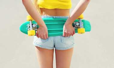 Junges Mädchen hält ein Mini Longboard