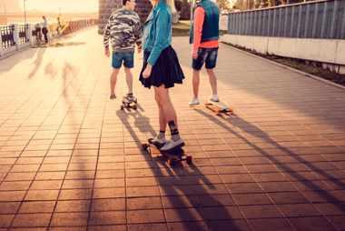 Drei Jugendliche mit Freeride Longboards in der Stadt