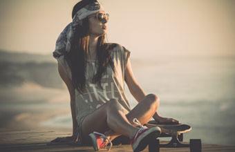 Ein Cruiser Longboard und ein Mädchen am Strand
