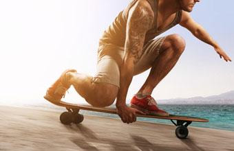 Ein Mann fährt mit einem Drop Down Longboard bergab