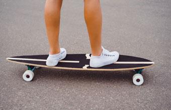 Anfänger beim Longboard kaufen auf der Straße