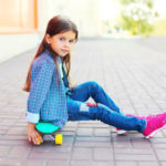 Kind auf Mini Longboard